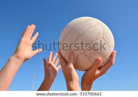 Female netball players holding a white ball outdoors. One of the players is about to shoot the ball into a hoop. - stock photo