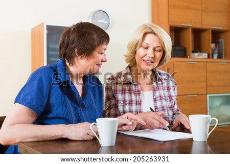 Female notary officer helping aged client drawing up of will