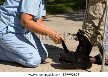 Female nurse adjusts strap on patient's ankle brace. - stock photo