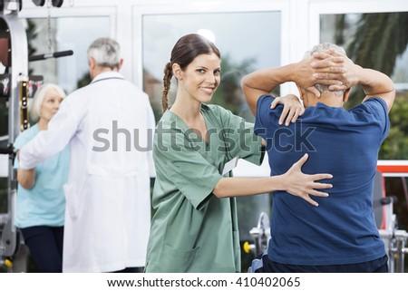 Female Nurse Assisting Senior Man In Back Exercise - stock photo