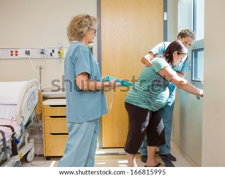 Female nurse carrying hospital gown for pregnant woman while colleague consoling her at window - stock photo