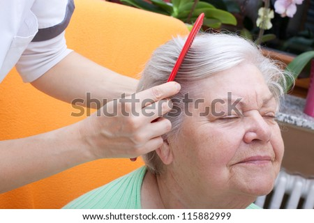 female nurse combing senior through her hair - stock photo