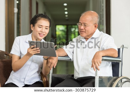 Female nurse discussing over digital tablet with senior man in wheelchair  at nursing home - stock photo