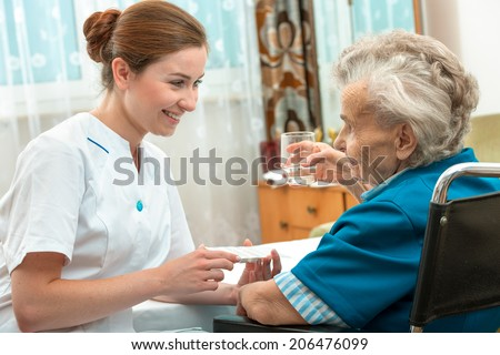 female nurse giving senior woman medical pills - stock photo