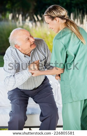 Female nurse helping senior man to sit on couch at nursing home - stock photo