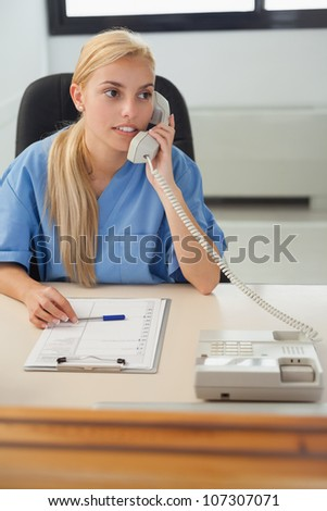 Female nurse holding a phone in hospital reception - stock photo