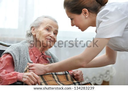 Female nurse is taking care of the senior woman - stock photo