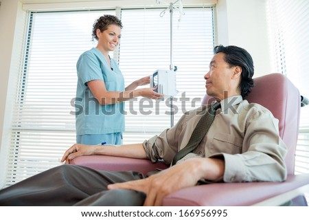 Female nurse looking at patient while adjusting IV machine for chemotherapy in hospital room - stock photo