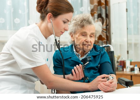 Female nurse measuring blood pressure of senior woman