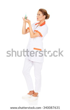 Female nurse or doctor with a syringe in hand. - stock photo