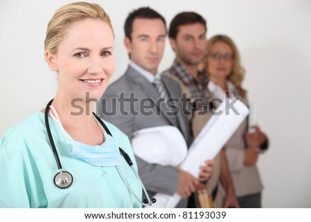 Female nurse stood next to four professionals from different backgrounds - stock photo