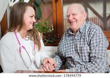 Female nurse taking care of senior old man - stock photo