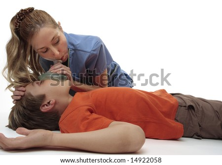 Female nurse using a resuscitation mask on a young unconscious boy.  Focus to boy. - stock photo