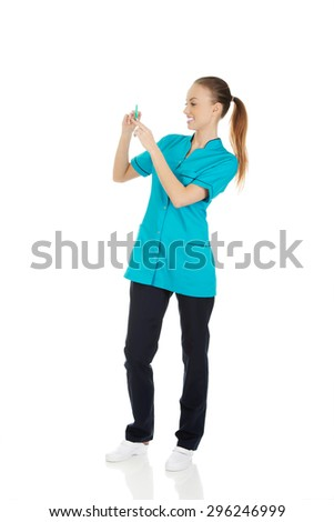 Female nurse with a syringe in hand.  - stock photo