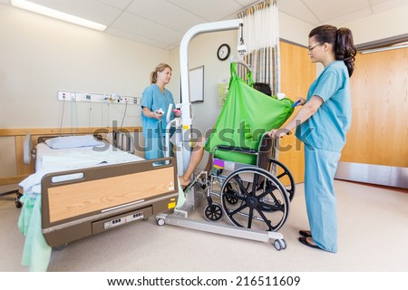 Female nurses transferring male patient from hydraulic lift to wheelchair in hospital - stock photo
