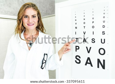 Female oculist doctor pointing at eye sight test chart and looking at camera - Optic medical concept in private clinic studio with young woman welcoming and cheering at patient - stock photo