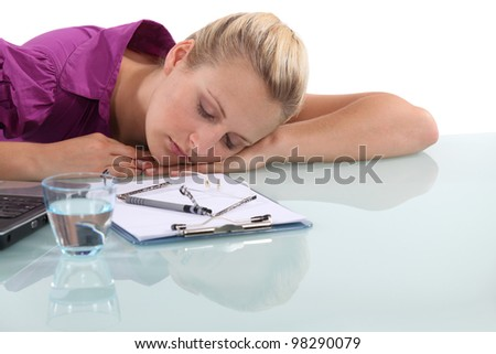 Female office worker asleep at desk - stock photo