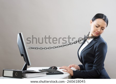Female office worker chained to her computer - stock photo
