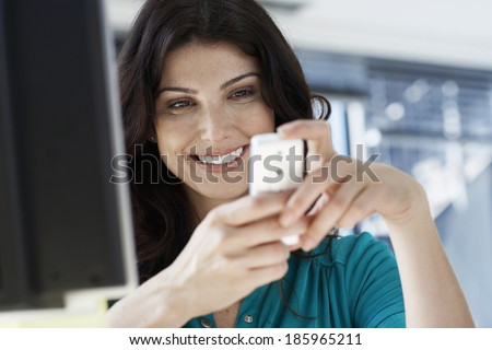 Female office worker text messaging