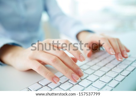 Female office worker typing on the keyboard - stock photo