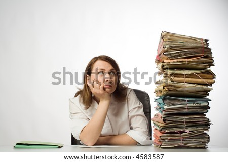 Female office worker with chin in hands staring at huge pile of files and folders awaiting her attention - stock photo