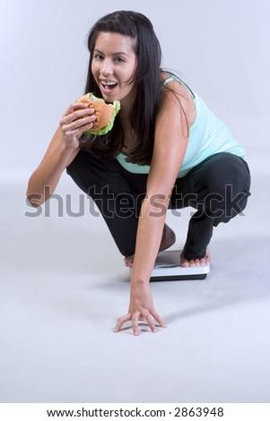 Female on weight scale eating hamburger - stock photo