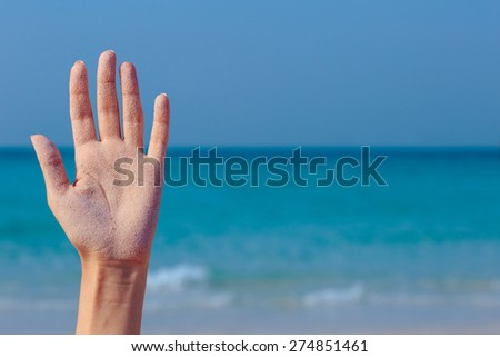 Female open hand on blue sea background