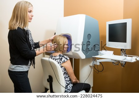 Female optometrist adjusting patient's head while looking at computer for retinal checkup - stock photo