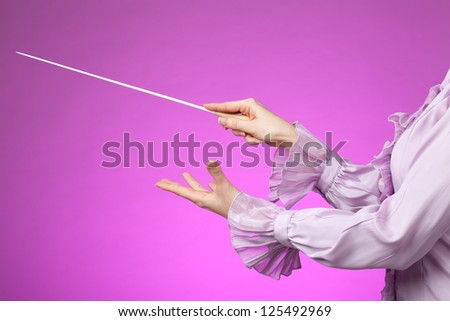 Female orchestra conductor hands, one with baton. Pink background. - stock photo