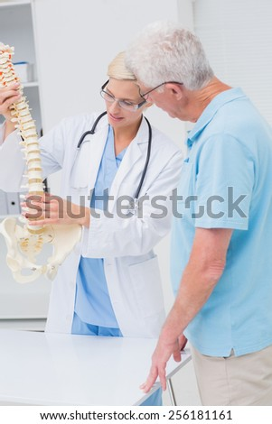 Female orthopedic doctor and senior patient discussing over anatomical spine in clinic - stock photo