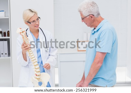 Female orthopedic doctor explaining anatomical spine to senior man in clinic - stock photo