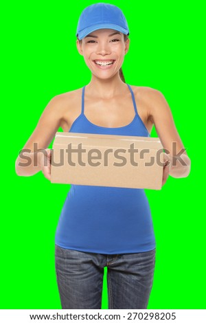 Female package delivery person giving packages wearing blue uniform. Woman courier smiling happy isolated on green screen chroma key background. Young mixed race Caucasian Chinese Asian female courier