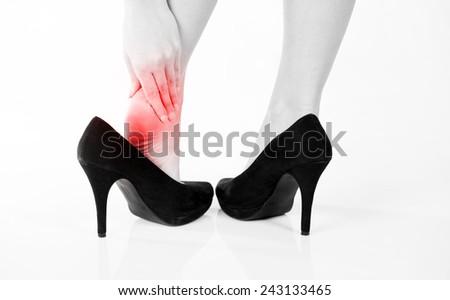 Female pain in heel when wearing high heels  - stock photo