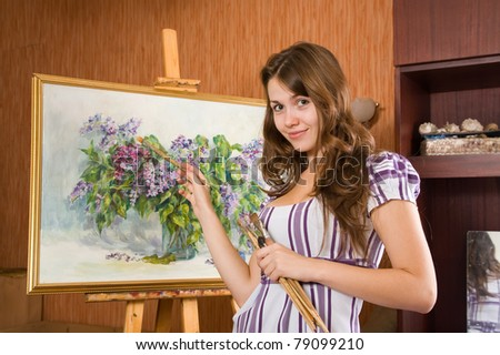 Female painter with brushes near  easel with picture of flowers in interior