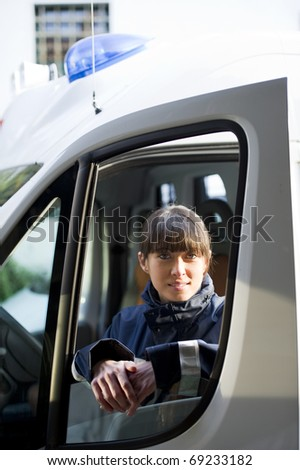 Female Paramedic Driving Ambulance - stock photo