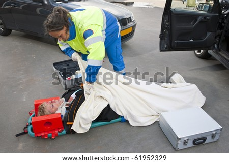 Female paramedic putting a blanket over an injured woman on a stretcher - stock photo