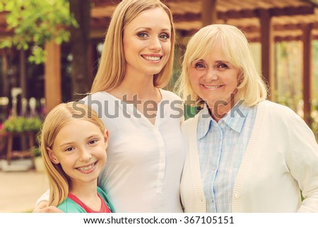 Female part of family. Three generations of family women bonding to each other and smiling while standing in front of their house - stock photo