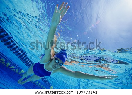 Female participant swimming under water in a swimming race - stock photo