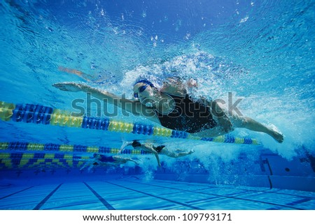 Female participants gushing through water in swimming competition - stock photo