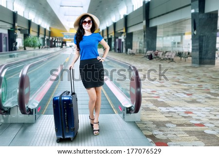 Female passenger with suitcase standing at the airport - stock photo