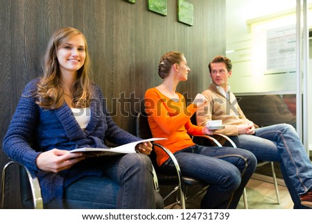 Female patient at reception of clinic looking at the viewer, in the background other people waiting for her treatment - stock photo