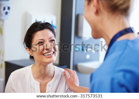Female Patient Being Reassured By Doctor In Hospital Room - stock photo