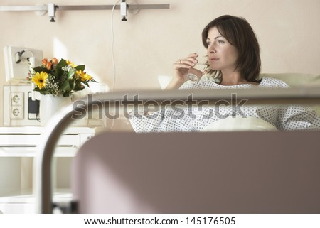 Female patient drinking water in the hospital bed - stock photo
