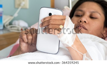 Female Patient In Hospital Bed Using smartphone  - stock photo