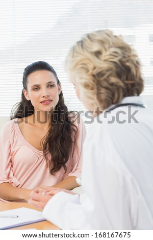 Female patient listening to doctor with concentration in medical office - stock photo