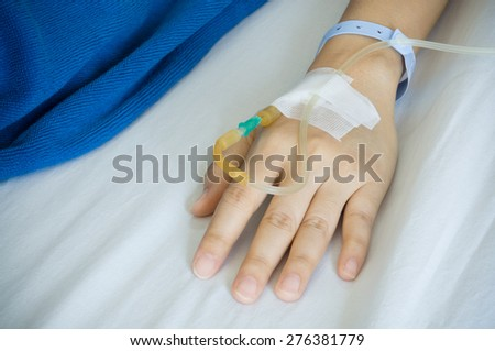 Female patient's hand recieving iv saline solution in hostpital. shoot on white bed background
