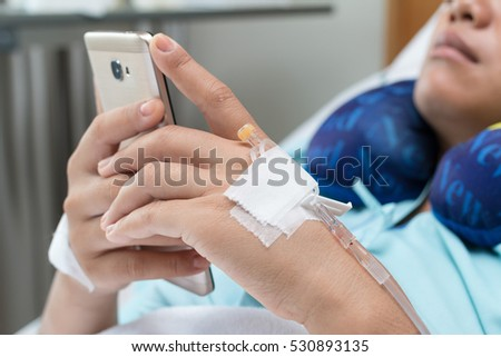 Female Patient Using Mobile Phone In Hospital Bed