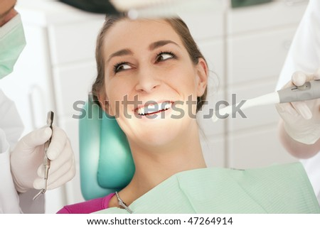 Female patient with dentist looking happy and smiling - obviously the examination yielded no result thus there is no need to drill - stock photo