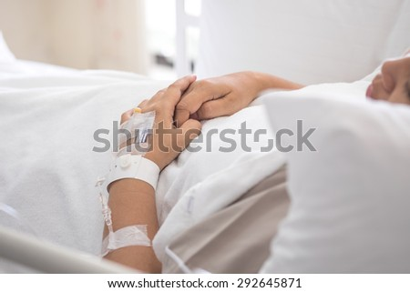 Female patient with IV drip needle lying on bed in hospital for medical background - stock photo