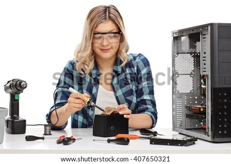 Female PC technician soldering a chip from a desktop computer isolated on white background - stock photo